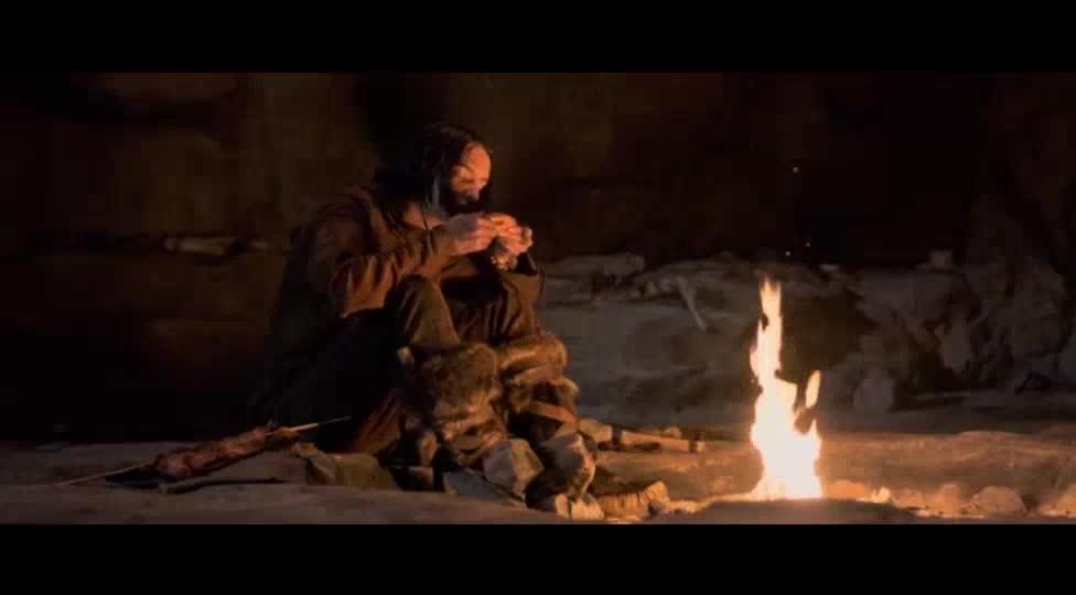 小伙围着火堆吃肉,狼却可怜巴巴在旁边看着
