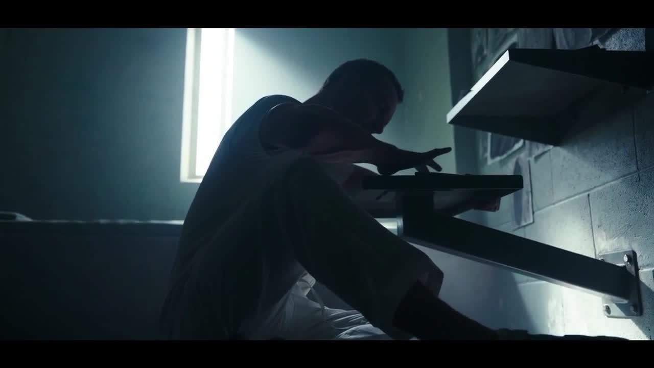 男子在黑暗的监狱里,坐着画奇怪的头像,西服男子进来找他