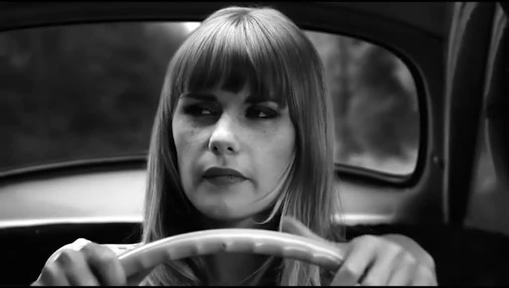 女人开车在路上,有一辆轿车快速超车后,返回跟踪她