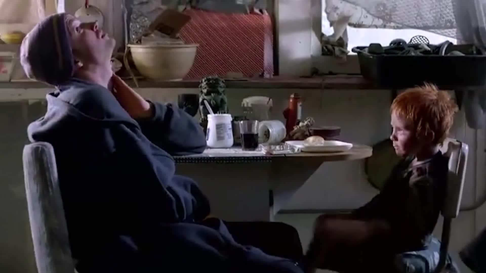 小伙无聊的看着小男孩吃饭,试图和小男孩互动,并成功逗笑了他